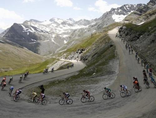 The pack of riders cycle in the Alps during the ninth stage of the 94th Tour de France